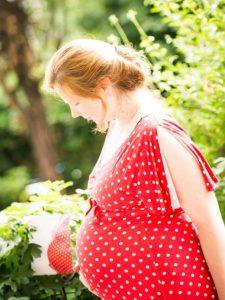 schwangere mit rotem kleid im garten